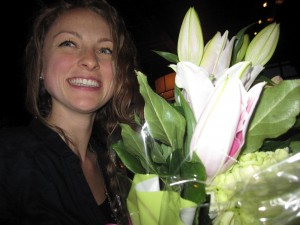 Erinn Weatherbie smiling and holding a bouquet of white flowers