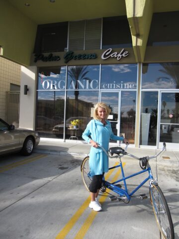 Kelly Childs wearing blue holding a two seater bike in front of Palm Greens cafe