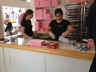 Workers building and packing boxes full of cupcakes at Georgetown Cupcakes
