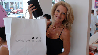 Kelly Childs holding up a Georgetown Cupcakes bag