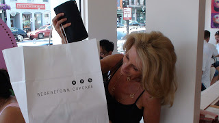 Kelly Childs inspecting a Georgetown Cupcakes bag