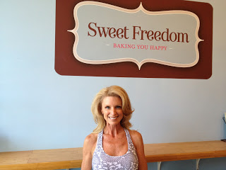 Kelly Childs standing in front of a Sweet Freedom Bakery sign