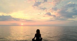 Kelly Childs meditating on a beach