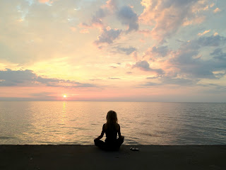 Kelly Childs meditating on a beach