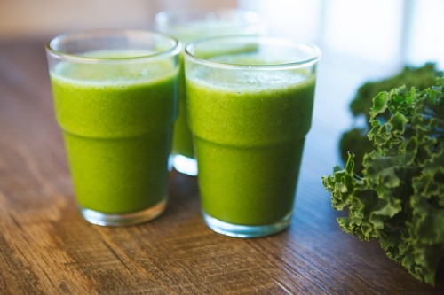 Three green smoothies made by Kelly Childs sitting on a wooden table