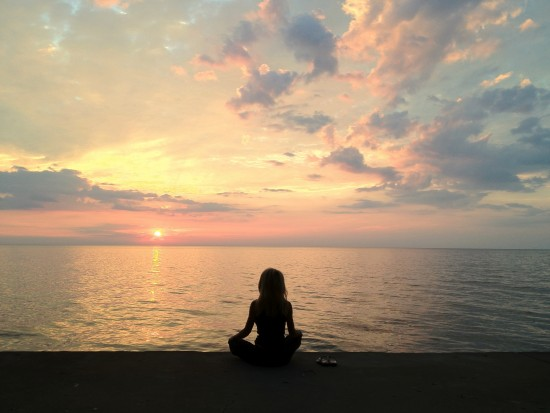 Kelly Childs meditating on the beach
