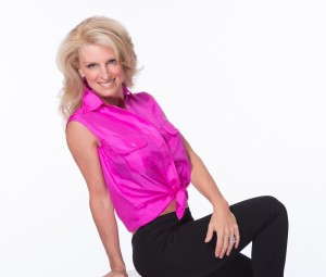 Kelly Childs leaning back wearing a pink vest