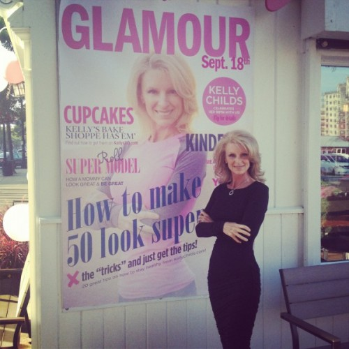 Kelly Childs standing beside the cover of GLAMOUR magazine
