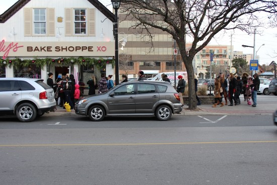 A line of people waiting out front Kelly's Bake Shoppe in the cold december weather