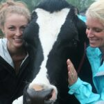 Erinn Weatherbie and Kelly Childs petting a milk cow